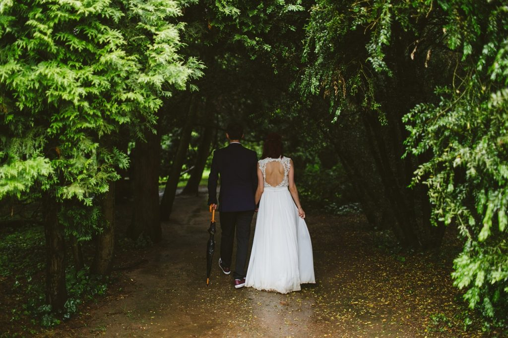 is rain on your wedding day good luck couple walking into forest with umbrella